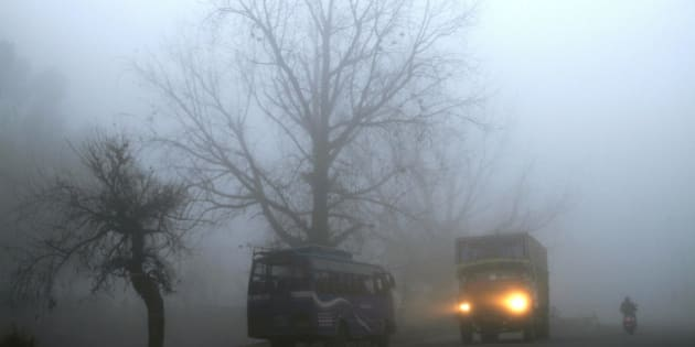 A truck passes amid morning fog on a national highway, near Jammu, India, Friday, Jan. 31, 2014. Dense fog enveloped most part of northern India disrupting rail, road and air traffic as cold conditions continue unabated, according to local reports. (AP Photo/Channi Anand)