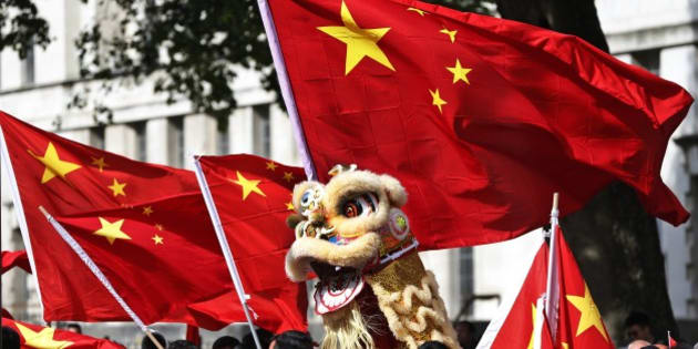 Chinese students, supporters of Chinese Prime Minister Li Keqiang, one holding a puppet depicting a dragon, wave their national flags as they gather at a counter-demonstration against a protest against the leader across the street from Downing Street in central London, where he was meeting with British Prime Minister David Cameron at his official residence, Tuesday, June 17, 2014. The Chinese leader met with Cameron and other senior government officials, and the two sides are expected to announce a slew of trade and investment deals. (AP Photo/Lefteris Pitarakis)