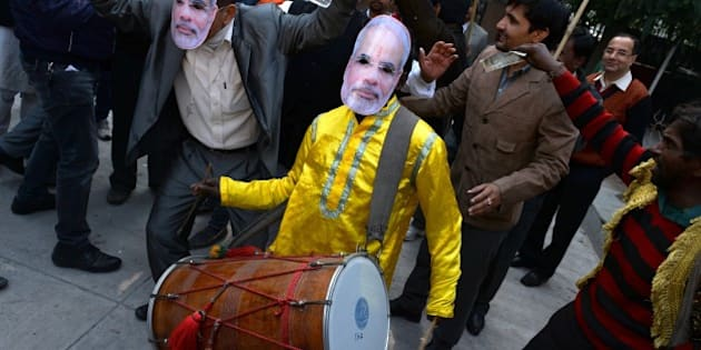 A traditional drummer wears a mask bearing the portrait of Indian Prime Minister Narendra Modi as Bharatiya Janata Party (BJP) supporters celebrate following the Jharkhand, and Jammu and Kashmir state assembly election results in New Delhi on December 23, 2014. Indian Prime Minister Narendra Modi's Hindu nationalist party made significant election gains in the restive Muslim-majority state of Jammu and Kashmir but will fall well short of a majority, according to partial results out December 23. AFP PHOTO / CHANDAN KHANNA        (Photo credit should read Chandan Khanna/AFP/Getty Images)