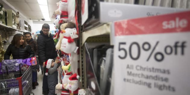 Anthony Pendon Jr. reaches for a ornament box as he shops with his family at Kmart on 34th Street, Thursday, Nov. 27, 2014, in New York. Millions of customers are expected to shop on Thanksgiving Day as many retailers remain open on a day traditionally reserved for spending time with family. (AP Photo/John Minchillo)