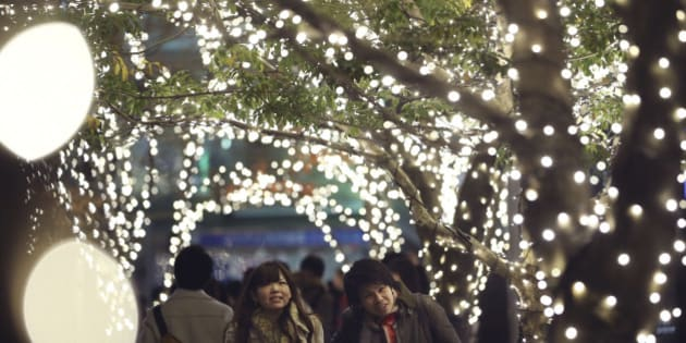 A couple walks through part of Christmas illuminations, lit by 280,000 LED lights, at Tokyo Midtown business and commercial complex in Tokyo, Saturday, Dec. 21, 2013. (AP Photo/Koji Sasahara)