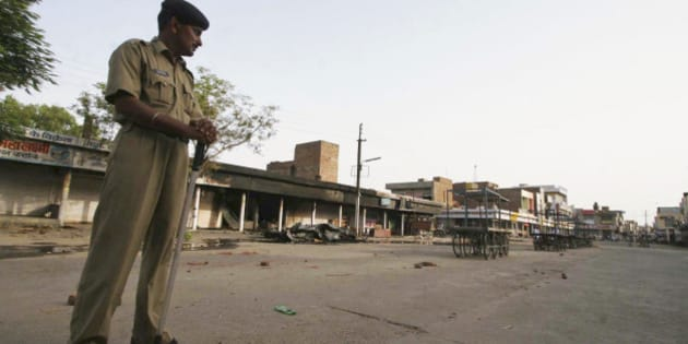 A policeman stands guard on a deserted street during a curfew in Dabwali town, Sirsa district, in the Indian state of Haryana, Saturday, July 19, 2008. The curfew was imposed after a clash between a group of Sikhs and supporters of a quasi-religious sect Dera Sacha Sauda left one dead and several injured in Sirsa district Friday. Seeking immediate arrest of the leader of the sect Gurmeet Ram Rahim Singh, radical Sikh organizations Saturday issued a ceasework call in Punjab and Haryana state on July 23. (AP Photo/Davinder Luther)