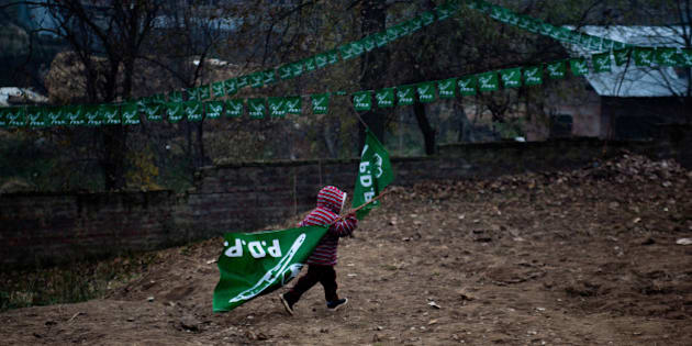 KOLGOM, KASHMIR, INDIA - NOVEMBER 27:  A child carrries a PDP flag during campaign rally for Mufti Mohammad Sayeed, former Chief Minister of Indian administered Kashmir and patron of Kashmir's main opposition political party, the Jammu and Kashmir People's Democratic Party (PDP), on November 27, 2014,  in Kolgom south of  Srinagar, the summer capital of Indian administered Kashmir, India. Amid tight security, Kashmiris will  cast their votes in the second phase of assembly elections in the strife torn Jammu and Kashmir, even as most pro-independence groups have asked people to boycott the five phased polls which will end on December 20 and the results would be announced on December 23  (Photo by Yawar Nazir/Getty Images