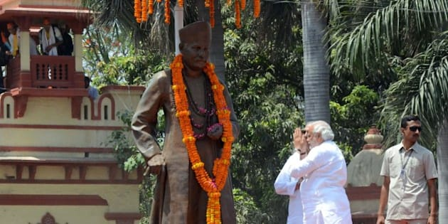 Chief Minister of the Indian state of Gujarat and Bharatiya Janata Party (BJP) prime ministerial candidate Narendra Modi (R) prays in front of a statue of former Hindu nationalist politician Madan Mohan Malviya during a rally in Varanasi on April 24, 2014. India's 814-million-strong electorate is voting in the world's biggest election which is set to sweep the Hindu nationalist opposition to power at a time of low growth, anger about corruption and warnings about religious unrest. AFP PHOTO/STR        (Photo credit should read STRDEL/AFP/Getty Images)