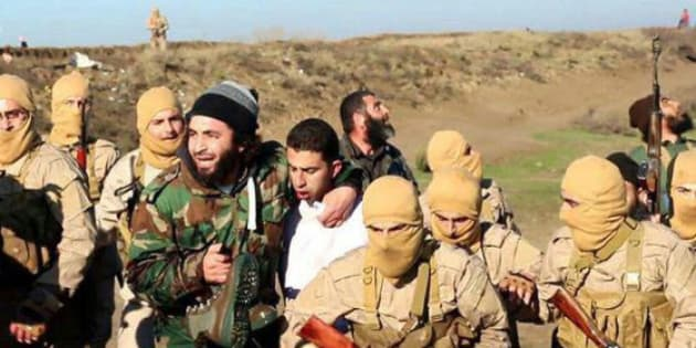 This image posted by the Raqqa Media Center of the Islamic State group, a militant extremist group, which has been authenticated based on its contents and other AP reporting, shows members of the Islamic State group while captured the pilot, center, wearing a white shirt in Raqqa, Syria, Wednesday, Dec. 24, 2014. Activists say that Islamic State fighters have shot down a warplane believed to be from the U.S.-led coalition over Syria. (AP Photo/Raqqa Media Center of the Islamic State group)