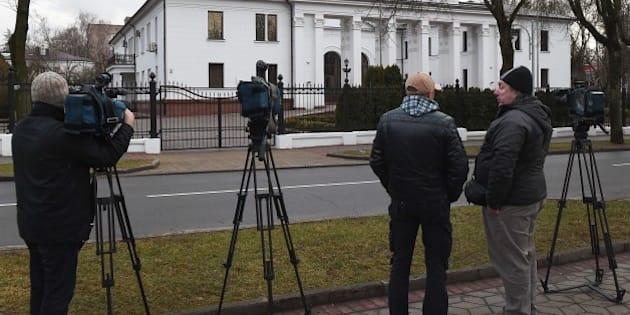 News cameramen wait outside the presidential residence in Minsk on December 24, 2014, as fresh round of peace talks of the trilateral contact group with Ukraine's pro-Russian rebels are set to take place in the Belarussian capital on December 24 and 26, to enforce a tenuous peace agreement reached at negotiations in Belarus in September. AFP PHOTO / MAXIM MALINOVSKY