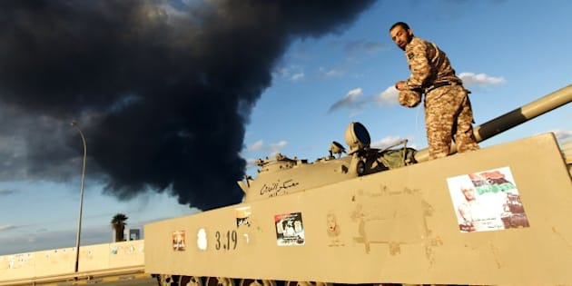 A member of the Libyan army stands on a tank as heavy black smoke rises from the city's port in the background after a fire broke out at a car tyre disposal plant during clashes against Islamist gunmen in the eastern Libyan city of Benghazi on December 23, 2014. Forces loyal to former general Khalifa Haftar and to internationally recognised Prime Minister Abdullah al-Thani have been battling for weeks against Islamists who have taken control of much of Libya's second city, and the capital Tripoli. AFP PHOTO / ABDULLAH DOMA        (Photo credit should read ABDULLAH DOMA/AFP/Getty Images)