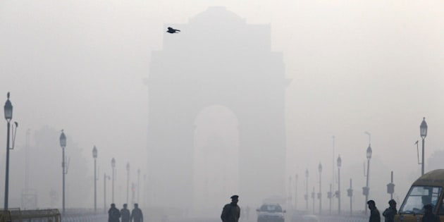 An Indian paramilitary force soldier watches army soldiers rehearse for the Republic Day parade amidst morning fog at India Gate, in New Delhi, India, Tuesday, Jan. 7, 2014. (AP Photo/Tsering Topgyal)