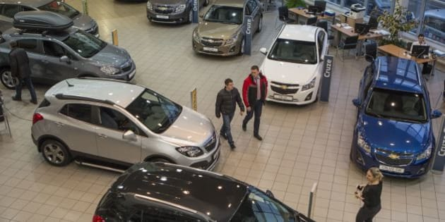 Customers examine cars on a display at an automobile dealership in Moscow, Russia, Saturday, Dec. 20, 2014.Shops selling a broad range of items were reporting record sales — some have even suspended operations, unsure of how far the ruble will sink. Apple, for one, has halted all online sales in Russia.(AP Photo/Denis Tyrin)