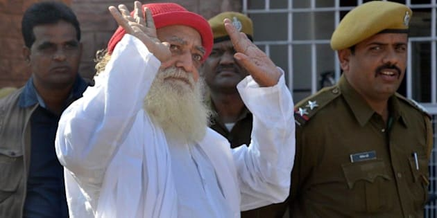 JODHPUR, INDIA - NOVEMBER 18: Asaram Bapu, Hindu preacher gestures to media persons as he returns after being produced at session court in connection with the case of sexual assault of a minor on November 18, 2013 in Jodhpur, India. Court dismissed as withdrawn the petitions moved by controversial self-styled godman Asaram. (Photo by Ramji Vyas/Hindustan Times via Getty Images)