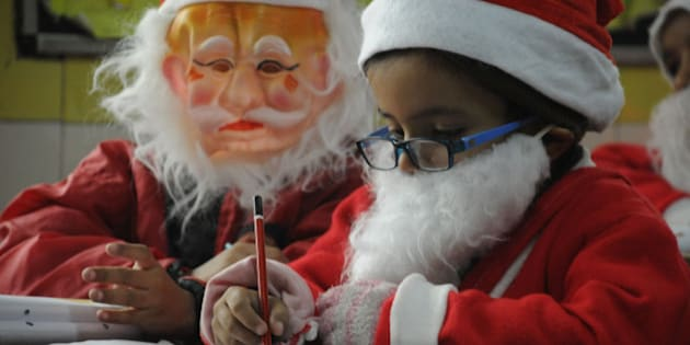 GURGAON, INDIA  DECEMBER 24: Children attending their classes dressed as Santa Claus dress at Euro International School on December 24, 2014 in Gurgaon, India. Christmas is celebrated with fanfare and zeal throughout the India by people of all religions and faiths. (Photo by Parveen Kumar/Hindustan Times via Getty Images)