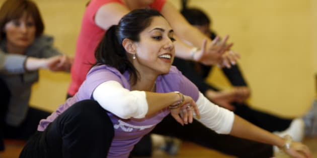 Reflected in a mirror on the walls of the dance studio, instructor Renu Kansal leads students in practicing Bollywood dance steps at a dance school in south Denver on Tuesday, Feb. 17, 2009. Drawn to the lavish dance numbers in films from India, or just bored with their gym workouts, people are flocking to Bollywood-style dance classes that mix traditional Indian folk dances with hip-hop moves. And the U.S. exercise industry is taking notice. (AP Photo/David Zalubowski)