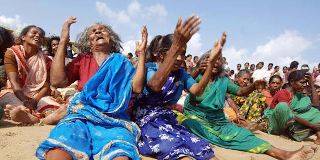 NAGAPATTINAM, INDIA:  Indian survivors of the December 2004 tsunami burst into tears after they performed a Puja (prayers) for their relatives killed in the tragedy on the beach in Nagapattinam some 350 kms south of Chennai, 26 December 2005.  India offered tearful tributes to the thousands killed in last year's tsunami with countrywide memorial services, silent marches and beachside ceremonies. India lost more than 16,000 people as villages were wiped out along its southern coast and on the Andaman and Nicobar island chain, and suffered material damage estimated by the United Nations at 2.5 billion dollars. In Nagapattinam, India's worst hit district in the southern state of Tamil Nadu, where almost 6,000 people died, each village found its own way to remember the destruction.                   AFP PHOTO/Dibyangshu SARKAR  (Photo credit should read DIBYANGSHU SARKAR/AFP/Getty Images)
