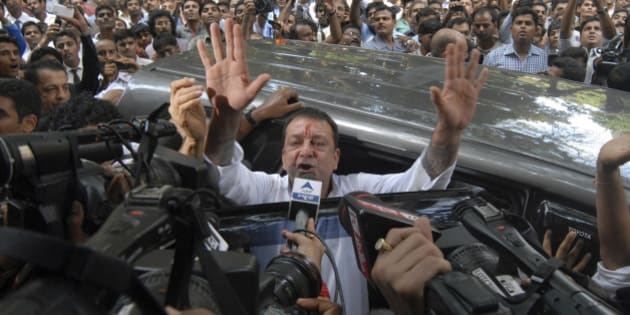 Bollywood star Sanjay Dutt, gestures to the media as he arrives at a court in Mumbai, India, Thursday, May 16, 2013. Dutt has been sentenced to five years in prison for a 1993 weapons conviction linked to a deadly terror attack in Mumbai that killed 257 people. The 53-year-old actor served 18 months in jail before being released on bail in 2007 pending an appeal. The Supreme Court reduced his prison sentence to five years from the six-year term initially handed down. (AP Photo/Rajanish Kakade)