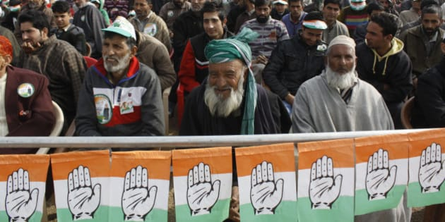 SRINAGAR, INDIA - NOVEMBER 21: Congress supporters listen to the speech by party president Sonia Gandhi during an election rally on November 21, 2014 in Bandipora, some 55 kms from Srinagar, India. Addressing the public meeting, Sonia Gandhi said that the BJP did not fulfill promises of relief and rehabilitation made to people of Kashmir after recent floods. She went on to saying that the BJP government in the Centre does not care about the prosperity of the state. (Photo by Waseem Andrabi/ Hindustan Times via Getty Images)