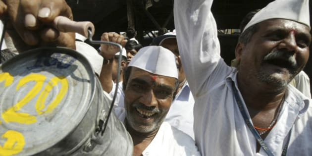 A lunch delivery man or 'Dabbawala' holds up a tiffin box as he participates in a session of 'Laughter' yoga in Mumbai, India, Friday, Feb. 22, 2008. The about 4,500 strong force of dabbawalas deliver home-cooked food to about 1,50,000 customers thoroughout Mumbai. Laughter yoga is believed to aid in relieving stress and increase a sense of well-being. (AP Photo/Gautam Singh)