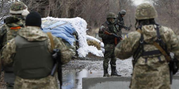 Ukrainian government army soldiers at a check-point near the village of Debaltseve, Donetsk region, eastern Ukraine Wednesday, Dec 24, 2014. Peace talks aimed at reaching a stable cease-fire in Ukraine between its government forces and pro-Russian armed groups began on Wednesday in Minsk, Belarus, with the discussions to include a pullout of heavy weapons and an exchange of war prisoners. (AP Photo/Sergei Chuzavkov)
