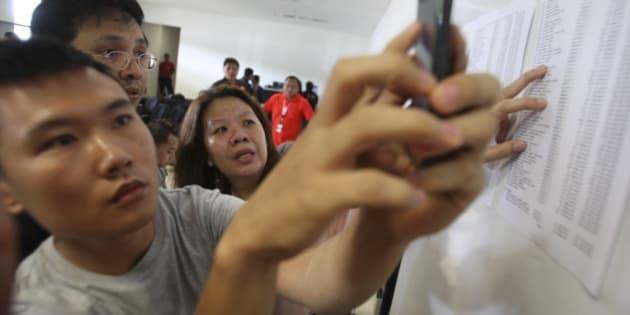 Relatives of the passengers onboard AirAsia flight QZ8501, check the plane's manifest at a crisis center set up by local authority at Juanda International Airport in Surabaya, East Java, Indonesia, Sunday, Dec. 28, 2014. The AirAsia plane with over 160 people onboard, lost contact with ground control on Sunday while flying over the Java Sea after taking off from the provincial city in Indonesia for Singapore. (AP Photo/Trisnadi)