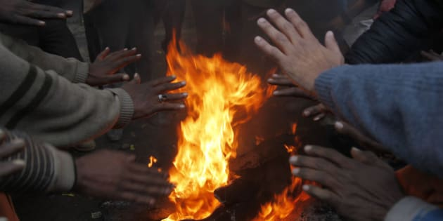 ALLAHABAD, INDIA - 2014/12/22: People warm themselves around a bonfire on a foggy and cold weather along the road  in Allahabad. (Photo by Ravi Prakash/Pacific Press/LightRocket via Getty Images)