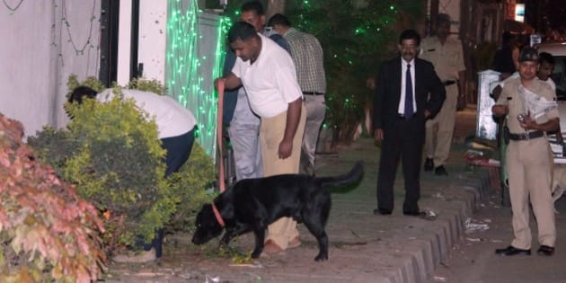 Bomb squad personnel along with sniffer dogs scour the blast site for evidence following a low intensity blast from an  Improvised Explosive Device (IED) which killed a woman and left three injured near a busy restaurant in the central business district of Bangalore, during late evening on December 28, 2014. AFP PHOTO/STR        (Photo credit should read -/AFP/Getty Images)