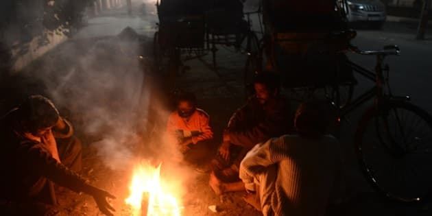 Indian rickshaw pullers warm themselves beside a fire on a pavement in Jalpaiguri on December 28, 2014. Many parts of northern India are experiencing dense foggy cold days with the resulting low visibility affecting road, rail and air traffic. AFP PHOTO/Diptendu DUTTA        (Photo credit should read DIPTENDU DUTTA/AFP/Getty Images)