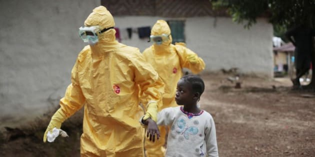 FILE - In this Sept. 30, 2014, file photo, Nine-year-old Nowa Paye is taken to an ambulance after showing signs of the Ebola infection in the village of Freeman Reserve, about 30 miles north of Monrovia, Liberia. (AP Photo/Jerome Delay, File)