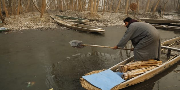 A Kashmiri boat man breaks the frozen surface of water of a Lake on a cold and foggy morning in Srinagar, in  India, Thursday, Dec. 25, 2014. Cold wave tightened its grip on the Kashmir valley as it continues to reel under intense cold wave for the past few days with widespread snowfall in the hilly areas. (AP Photo/Mukhtar Khan)