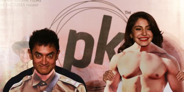"Bollywood actors Aamir Khan, left, and Anushka Sharma pose with movie character cut-outs during the teaser launch of their upcoming film ""PK"" in Mumbai, India, Thursday, Oct. 23, 2014. The movie is scheduled for release on Dec. 19. (AP Photo/Rafiq Maqbool)"