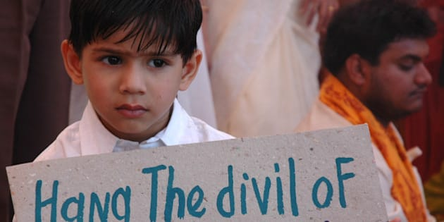 A boy holds a placard as he attends a prayer for world peace at a school in Ahmadabad, India, Friday, Feb. 16, 2006. The placard refers to the Nithari killing case where a businessman Moninder Singh Pandher and his servant Surender Kohli are charged of the death of up to 38 women and children after the victims were kidnapped and raped. (AP Photo/Ajit Solanki)