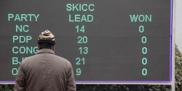 SRINAGAR, INDIA - DECEMBER 23: A man looks at a result board in Sher-e-Kashmir international convention center (SKICC) where counting center is stationed as the vote counting begin in Srinagar, India on December 23, 2014. (Photo by Faisal Khan/Anadolu Agency/Getty Images)