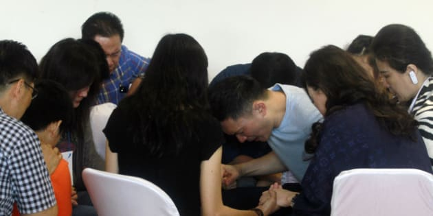 Relatives and next-of-kin of passengers on the AirAsia flight QZ8501 offer prayers, waiting for the latest news on the search of the missing jetliner at Juanda International Airport in Surabaya, East Java, Indonesia, Tuesday, Dec. 30, 2014.  More planes will be in the air and more ships on the sea Tuesday hunting for AirAsia Flight 8501 in a widening search off Indonesia that has dragged into a third day without any solid leads. Flight 8501 vanished Sunday in airspace thick with storm clouds on its way from Surabaya, Indonesia, to Singapore.(AP Photo/Firdia Lisnawati)