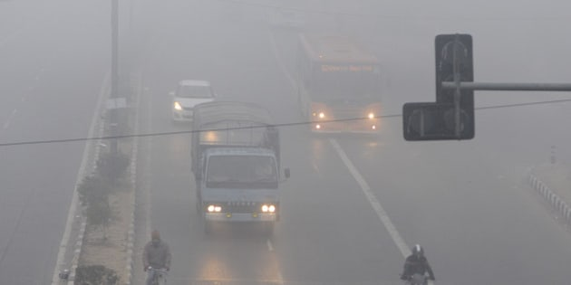 NEW DELHI, INDIA - DECEMBER 29: People commute amidst dense fog on a cold morning on December 29, 2014 in New Delhi, India. It was a chilly morning with minimum temperature settling three notches below normal at 4.8 degrees Celsius while dense fog enveloped the city, delaying 98 trains and several flights. (Photo by Sushil Kumar/Hindustan Times via Getty Images)