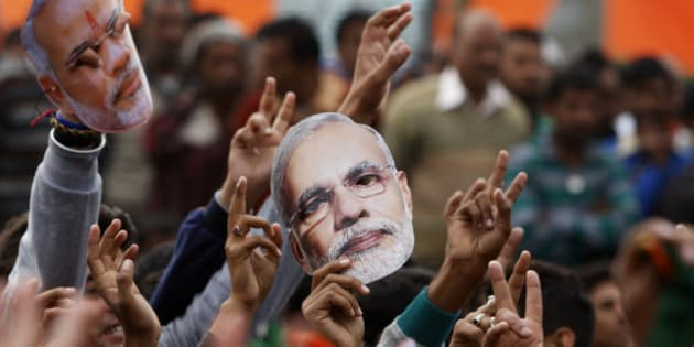 Supporter of India's ruling Bharatiya Janata Party (BJP) hold up masks of Prime Minister Narendra Modi during an election campaign rally in Kathua, about 90 kilometers from Jammu, India, Saturday, Dec.13, 2014. The final two phases of the five-phased state elections of Jammu and Kashmir will be held on Dec. 14 and 20. (AP Photo/Channi Anand)