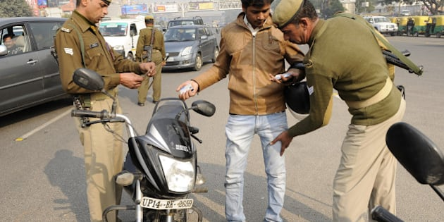 NOIDA, INDIA - DECEMBER 29: Police personnel checking a commuter as security has been tightened in the city after high alert was declared following a bomb blast at Bengaluru on December 29, 2014 in Noida, India. Security has been stepped up major cities of the country in the run up to the New Year celebrations following a bomb blast in Bengaluru. (Photo by Burhaan Kinu/Hindustan Times via Getty Images)