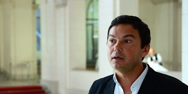 French economist and author Thomas Piketty speaks to journalists as he poses for a photographer following a discussion with German Vice Chancellor, Economy and Energy Minister at the Economy Ministry in Berlin November 7, 2014.  AFP PHOTO / JOHN MACDOUGALL        (Photo credit should read JOHN MACDOUGALL/AFP/Getty Images)