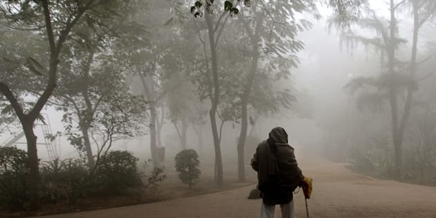 NEW DELHI, INDIA - DECEMBER 29: An old man doing his morning walk in park amidst dense fog on a cold morning on December 29, 2014 in New Delhi, India. It was a chilly morning with minimum temperature settling three notches below normal at 4.8 degrees Celsius while dense fog enveloped the city, delaying 98 trains and several flights. (Photo by Subrata Biswas/Hindustan Times via Getty Images)