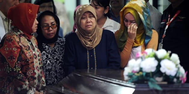 SURABAYA, INDONESIA - JANUARY 01:  Hayati Lutfiah Hamid's (C), the mother of the first identified victim of the AirAsia flight QZ8501, cries during a handover ceremony from AirAsia to her family on January 1, 2015 in Surabaya, Indonesia.  A massive recovery operation is underway in waters off Borneo to recover bodies and debris from the missing AirAsia plane.  AirAsia announced that flight QZ8501 from Surabaya to Singapore, with 162 people on board, lost contact with air traffic control at 07:24 a.m. local time on December 28.  (Photo by Robertus Pudyanto/Getty Images)