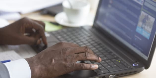 BONN, GERMANY - AUGUST 19: Hands of an African businessman on a laptop during a business meeting on August 19, 2014, in Bonn, Germany. Photo by Ute Grabowsky/Photothek via Getty Images)***Local Caption***