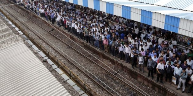Commuters wait for local trains in Mumbai, India, Tuesday, July 8, 2014. India's new rail minister Sadananda Gowda on Tuesday proposed allowing foreign investment to modernize the country's cash-strapped state railways. India has one of the world's largest railways, which transports 23 million passengers a day. Indian Railways is one of the world's biggest employers with more than 1.3 million employees. The network lost 300 billion rupees ($5 billion) last year. (AP Photo/Rajanish Kakade)