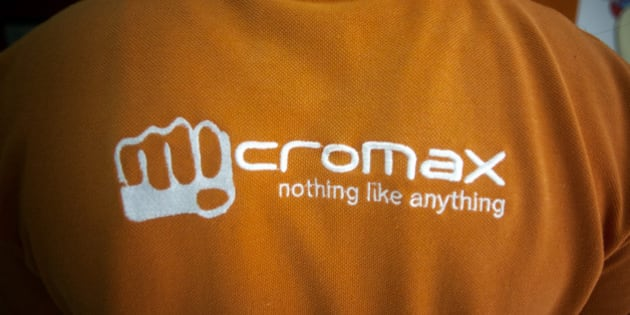 The MicroMax Informatics Ltd. logo is displayed on a employee's shirt at the company's store in New Delhi, India, on Tuesday, April 9, 2013. Apple Inc. and Samsung Electronics Co. are being outpaced in the fast-growing Indian smartphone market by aggressive local competitors Micromax and Karbonn Mobiles India Pvt. Ltd. Photographer: Prashanth Vishwanathan/Bloomberg via Getty Images
