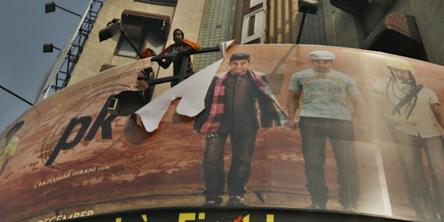 NEW DELHI, INDIA - DECEMBER 30: Poster of Aamir Khan-starrer film PK torn by activists of rightwing organizations Bajrang Dal and Hindu Sena outside Delite Cinema Theater on December 30, 2014 in New Delhi, India. Right-wing outfits accused Aamir Khan-starrer PK of hurting religious sentiments of the majority community demanded a ban on the film. Bollywood and theatre owners came out openly in support of the hugely successful Hindi film which takes a hard-hitting swipe at organised religion and godmen. (Photo by Raj K Raj/Hindustan Times via Getty Images)
