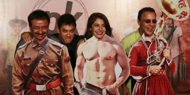 """Bollywood Director Rajkumar Hirani, left, Bollywood actors Aamir Khan, second left, Anushka Sharma, second right, and producer Vidhu Vinod Chopra pose in front of movie character cut-outs during the teaser launch of their upcoming film """"PK"""" in Mumbai, India, Thursday, Oct. 23, 2014. The movie is scheduled for release on Dec. 19. (AP Photo/Rafiq Maqbool)"""