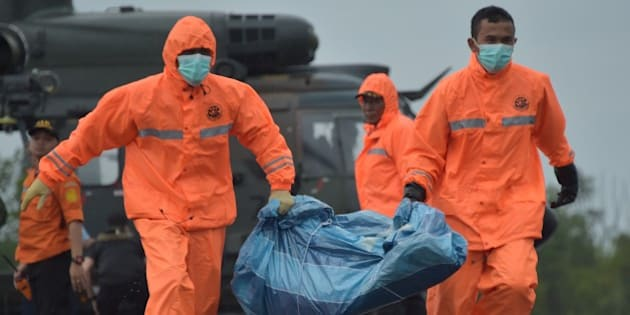Members of an Indonesian search and rescue team carry items for investigation, found during the search operation for the missing AirAsia flight 8501, after being delivered by a Singapore Super Puma helicopter from the Republic of Singapore Air Force (RSAF) RSS Persistence in Pangkalan Bun on January 4, 2015.  Weather was the 'triggering factor' in the crash of AirAsia Flight 8501 with icing likely causing engine damage, Indonesian officials said, as rough seas on January 4 hampered the search for bodies and the sunken wreckage. AFP PHOTO / ADEK BERRY        (Photo credit should read ADEK BERRY/AFP/Getty Images)