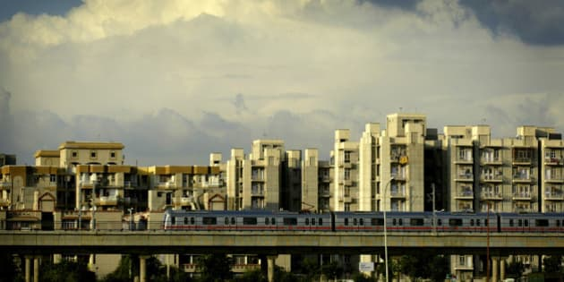 INDIA - AUGUST 05:  A New Delhi Metro Train passes in front of new apartment buildings in the township of Dwarka, in New Delhi, India, Saturday, August 5, 2006. National Housing Bank, India's monopoly lender to home mortgage companies, plans to borrow for the first time from international agencies such as the World Bank to meet rising demand for funds, Chairman S. Sridhar said.  (Photo by Amit Bhargava/Bloomberg via Getty Images)