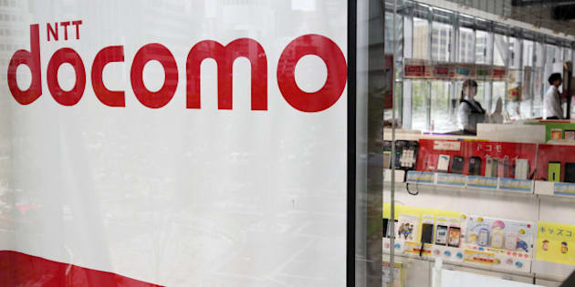 The NTT Docomo Inc. logo is displayed in the window of one of the company's stores in Tokyo, Japan, on Tuesday, June 10, 2014. NTT Docomo, Japan's largest wireless carrier by subscribers, began offering Apple Inc's iPad today. Photographer: Tomohiro Ohsumi/Bloomberg via Getty Images