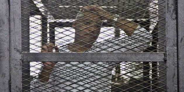 """Canadian-Egyptian acting Al-Jazeera bureau chief Mohammed Fahmy appears in a defendant's cage in a courthouse near Tora prison along with other defendants during a trial on terror charges in Cairo, Egypt, Saturday, May 3, 2014. Fahmy made a rare appeal to the judge from outside of the defendants' cage, at the end of which the judge wished him a """"happy"""" World Press Freedom Day. In his brief plea Saturday, Fahmy stood directly before the judge's bench. Fahmy said journalists have to speak to all sides to do their jobs. (AP Photo/Hamada Elrasam)"""