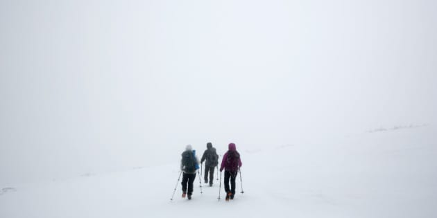 In this Saturday, April 5, 2014 photo, climbers Ania Kowalczyk, Marielle Bergeron and Lucy Bergeron, all of Quebec City, search for a trail marker during a whiteout caused by freezing fog, less than a mile from the summit of Mount Adams in New Hampshire. Winter weather, which often lasts well into spring in the Presidential Range, prompted the group to turn back. (AP Photo/Robert F. Bukaty)