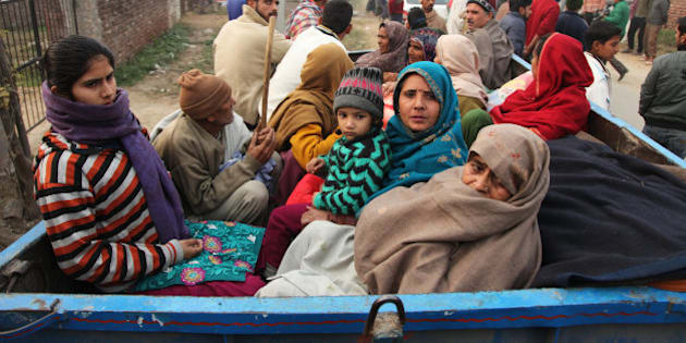 Indian villagers sit in the back of a vehicle as they flee their homes fearing firing from the Pakistan side of the border at Bainglad village in Samba sector, about 52 Kilometers from Jammu, India, Saturday, Jan. 3, 2015. Pakistani and Indian border guards traded artillery fire along the disputed border region of Kashmir, killing two people and wounding eight, officials said Saturday. (AP Photo/Channi Anand)