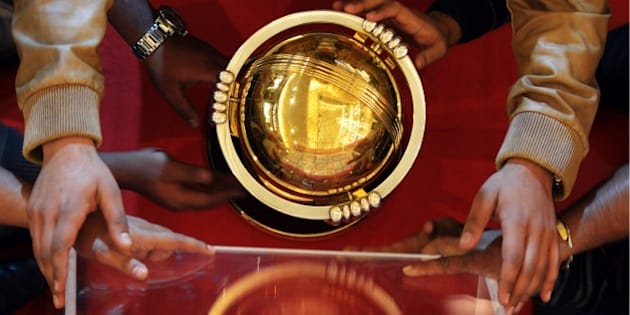 An Indian official adjusts a glass case over the ICC Cricket World Cup trophy on display at a shopping centre as a part of a promotional campaign in Kolkata on January 2, 2015.  The 11th ICC Cricket World Cup is scheduled to be jointly hosted by Australia and New Zealand from 14 February - 29 March 2015.   AFP PHOTO / Dibyangshu SARKAR        (Photo credit should read DIBYANGSHU SARKAR/AFP/Getty Images)