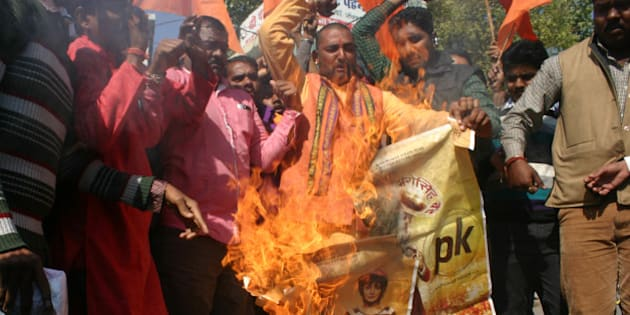 BHOPAL, INDIA - DECEMBER 28: Bajrang Dal activists burning the poster of Aamir Khan-starrer film PK outside Jyoti Talkies on December 28, 2014 in Bhopal, India. Accusing Aamir Khan-starrer PK of hurting religious sentiments of the majority community, right-wing outfits accused Aamir Khan-starrer PK of hurting religious sentiments of the majority community demanded a ban on the film. (Photo by Bidesh Manna/Hindustan Times via Getty Images)